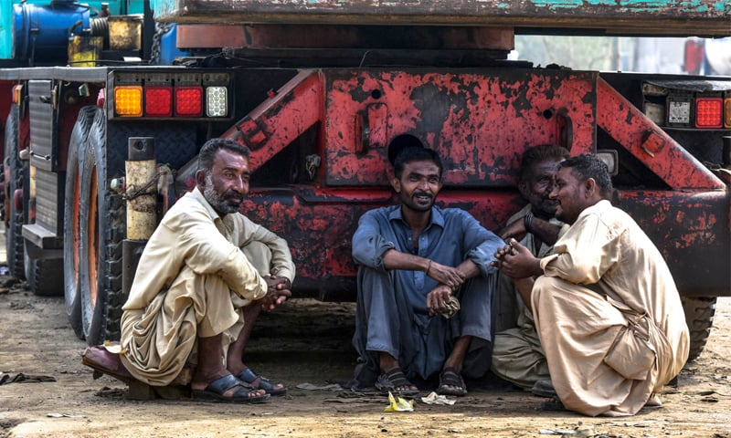 Four labourers sit in the shade of a truck in Karachi