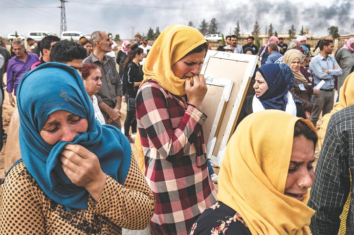 TAL TAMR (Syria): Mourners attend on Saturday the funeral of civilians and fighters who died during the recent attacks by Turkish-led forces on the Syrian border town of Ras al-Ain.—AFP