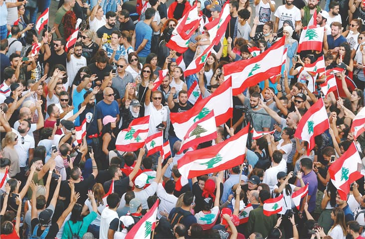 BEIRUT: Demonstrators carry national flags during an anti-government protest on Saturday.—Reuters