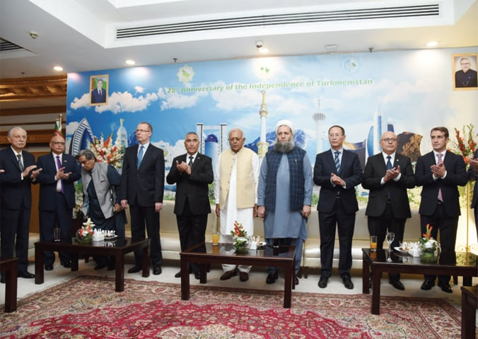 Federal ministers Maulana Noorul Haq Qadri and Ghulam Sarwar Khan, Turkmen Ambassador Atadjan Movlamov and other guests stand for national anthems of Pakistan and Turkmenistan at a reception in Islamabad.