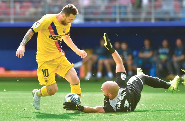 EIBAR: Barcelona's Lionel Messi attempts to dribble past Eibar goalkeeper Marko Dmitrovic during their La Liga match at the Ipurua Stadium.—AFP