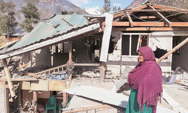 A WOMAN stands in front of her damaged house in Jura, a village in Azad Kashmir's Neelumvalley.—AFP
