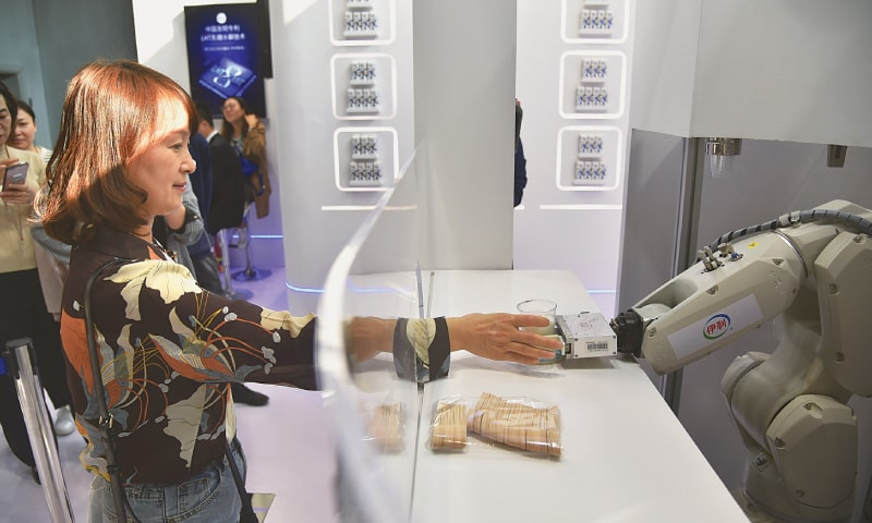 WUZHEN (China): A woman receives a glass of milk served by a robot at a stand during the Sixth World Internet Conference here on Sunday.—AFP