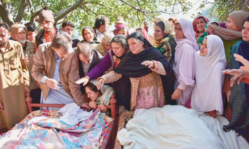 Relatives mourn beside the bodies of those who lost their lives in Indian shelling in Jura village.—AFP