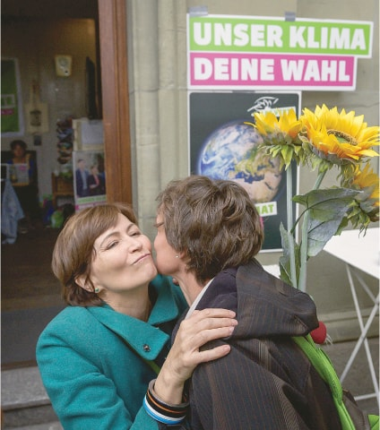 """BERN: A supporter congratulates Swiss Green Party President Regula Rytz while standing next to a placard reading in German: """"Our climate, your ballot"""".—AFP"""