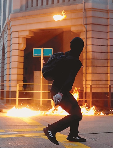 A protester throws a petrol bomb at a police station during the protest.—Reuters