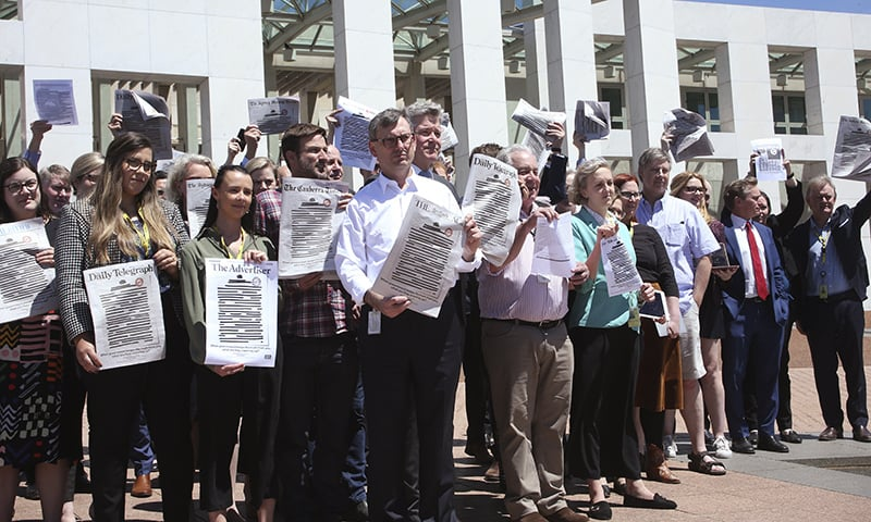 Journalists hold up newspapers with redacted front pages outside Parliament House in Canberra, Australia, on Monday. — AP