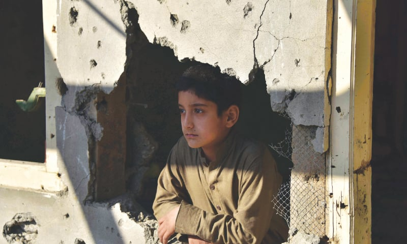 A Kashmiri boy looks out from his damaged house after cross-border shelling in Jura, a village of Neelum valley in Azad Jammu and Kashmir, on Monday.—AFP