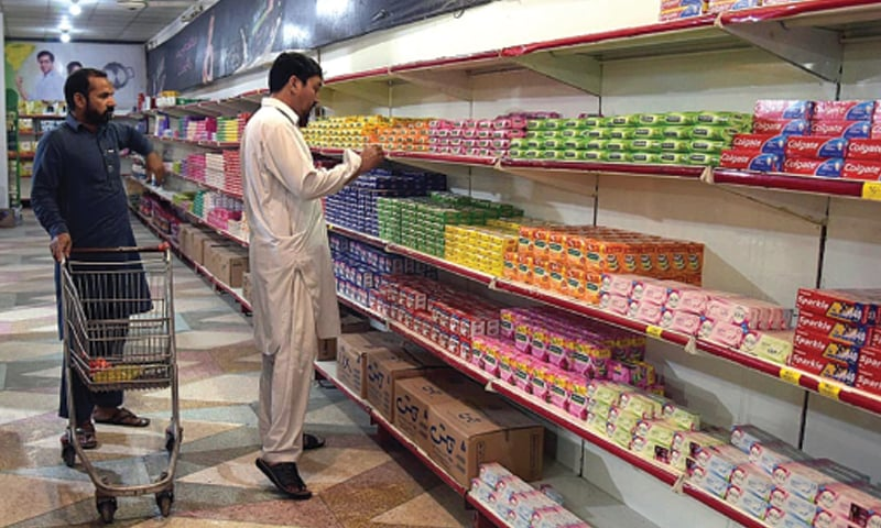 LAHORE: Buyers are selecting household items from a rack at a utility store. Poor quality of goods and little price differential has forced many regular customers to purchase items from the open market.—APP
