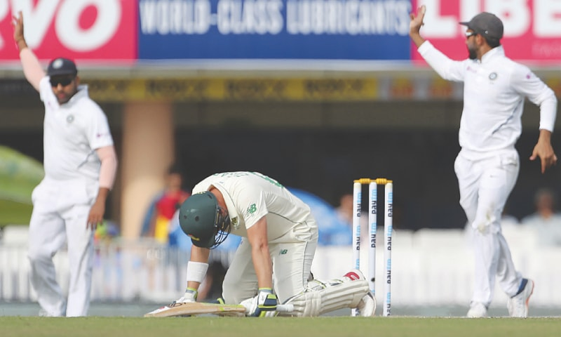 SOUTH African opener Dean Elgar stumbles after being hit by Indian pacer Umesh Yadav during the third Test on Monday.—AP