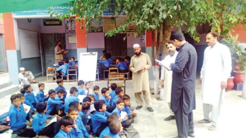 Due to shortage of classrooms, boys sit in the open at Government Boys High School Shahiya. — Dawn