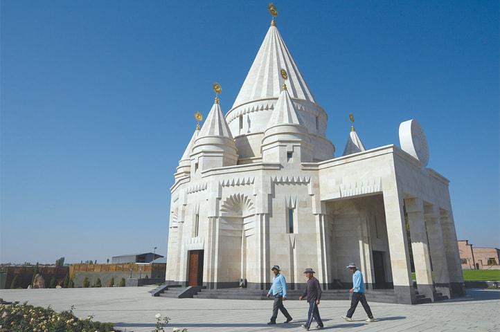 AKNALICH (Armenia): People walk past the new Yazidi temple.—AFP