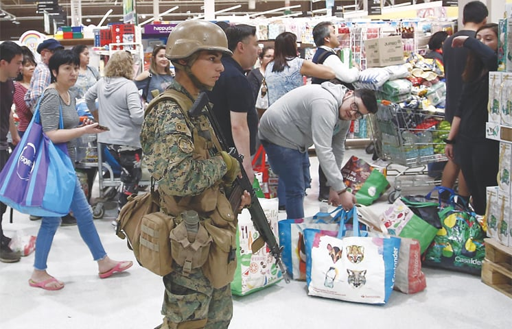SANTIAGO: A military policeman stands guard at a supermarket as customers wait in line on Monday.—AP