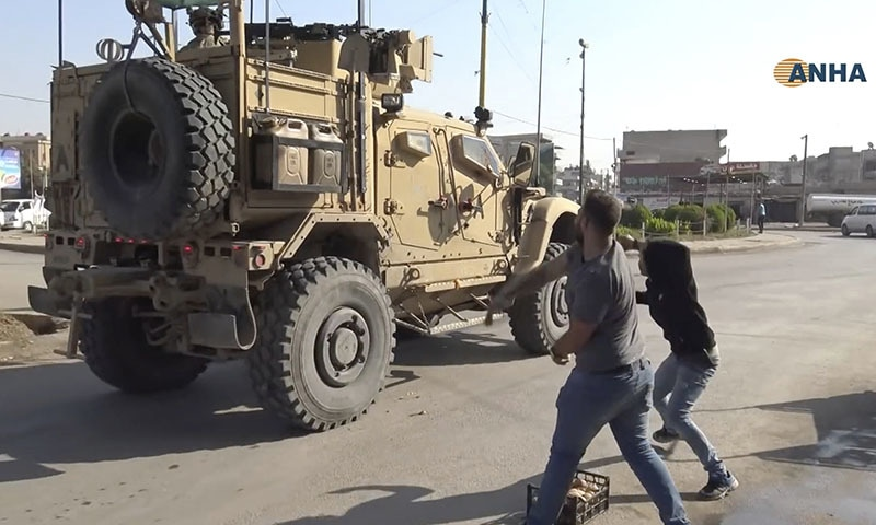 In this frame grab from video provided by Hawar News, ANHA, the Kurdish news agency, residents who are angry over the US withdrawal from Syria hurl potatoes at American military vehicles in the town of Qamishli, northern Syria on Monday. — ANHA via AP