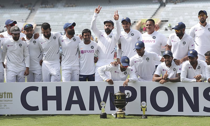 Members of Indian team pose with the winners trophy as captain Virat Kohli flashes victory sign after their win on the fourth day of third and last cricket test match between India and South Africa in Ranchi, India on October 22, 2019. — AP