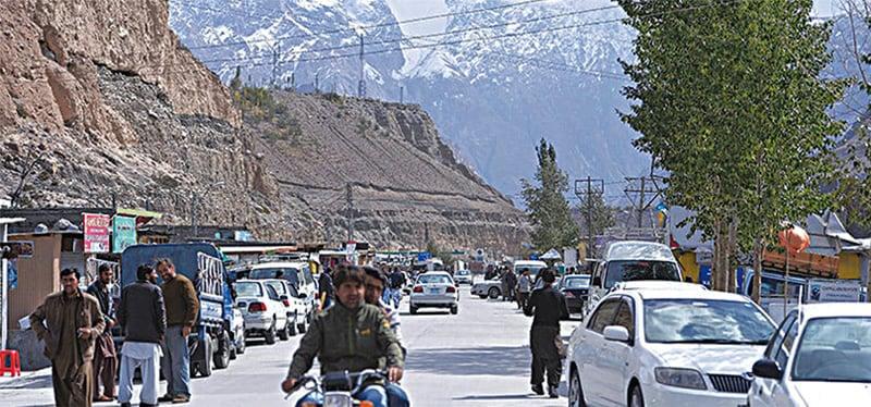 ہنزہ وادی کے سرحدی قصبے سوست میں مقامی افراد اور سیاح اپنے کاموں میں مصروف ہیں— محمد عارف/وائٹ اسٹار