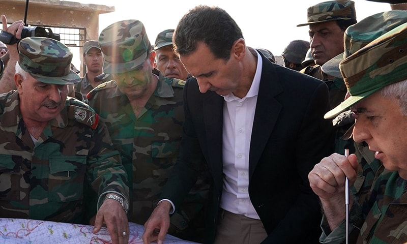 A handout picture released by the official Facebook page for the Syrian Presidency on Monday shows Syrian President Bashar al-Assad consulting a military map with  army officers in Al-Hbeit on the southern edges of the Idlib province. — AFP