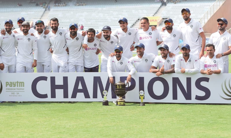 RANCHI: Members of Indian squad pose with the trophy after their victory in the third Test against South Africa on Tuesday.—AP