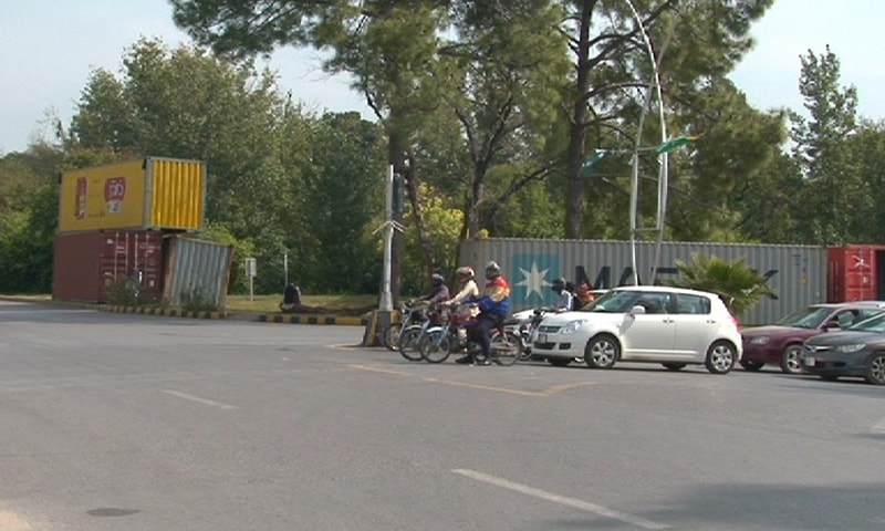 Motorists pass by containers that have been brought in to block roads leading to the Red Zone. — Photo provided by author