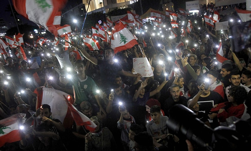 Lebanese protestors gather during demonstrations to demand better living conditions and the ouster of a cast of politicians who have monopolised power and influence for decades, on October 22 in the southern city of Sidon. — AFP