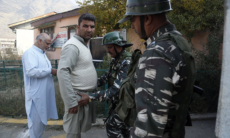 An Indian paramilitary soldier frisks a Kashmiri village council member outside a polling station on the outskirts of Srinagar, Indian-occupied Kashmir, on Thursday. — AP