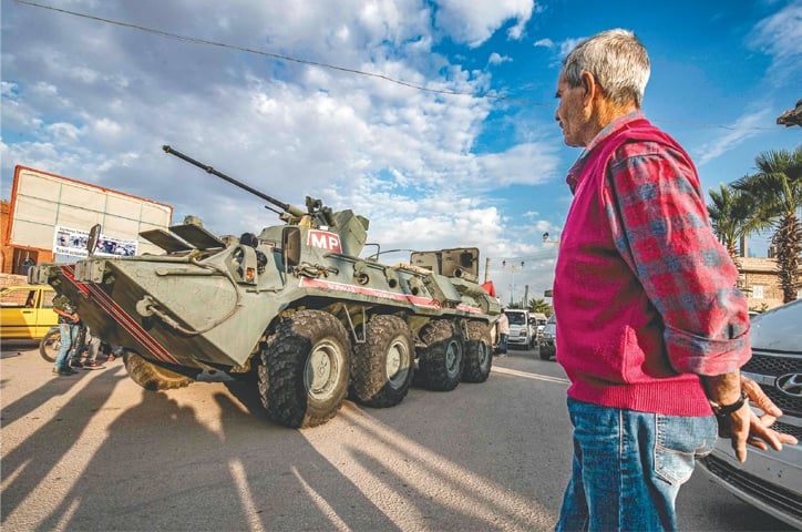 A man watches as a Russian military police armoured vehicle passes through a street in the north-eastern Syrian town of Amuda, in Hasakeh province, as part of a joint patrol between Russian forces and Syrian Kurdish internal security forces near the border with Turkey.—AFP
