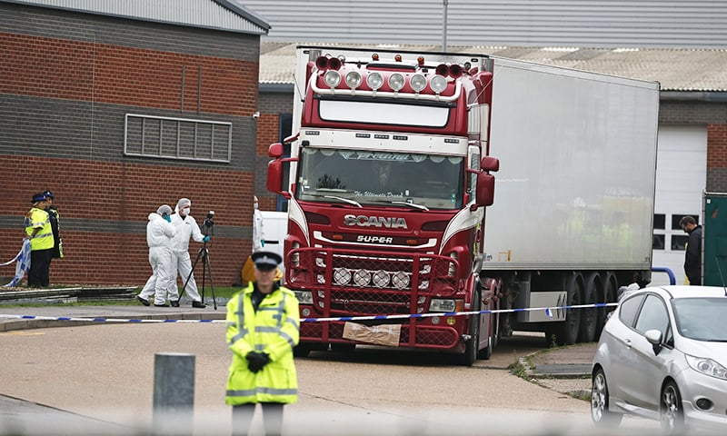 In this October 23 file photo, police forensic officers attend the scene after a truck was found to contain a large number of dead bodies, in Thurrock, South England. — AP