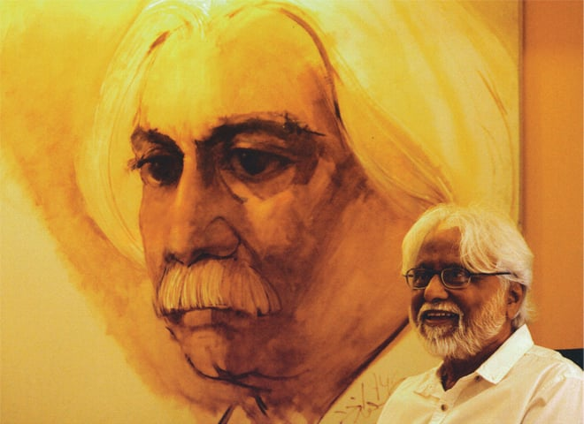 Adil Salahuddin in front of a portrait of himself by Saeed Akhtar | Photograph by Manisha G Baswani, from Message Sent: The Life and Works of Adil Salahuddin