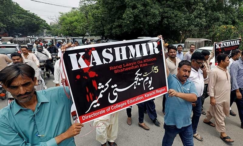 Demonstrators hold signs and chant slogans as they march in solidarity with the people of occupied Kashmir, during a rally in Karachi on August 5. — Reuters/File