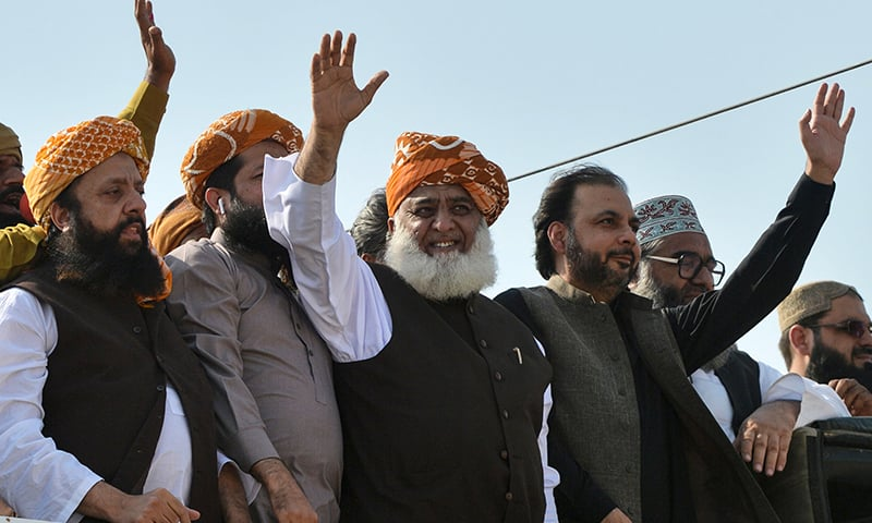 "Maulana Fazlur Rehman, chief of the Jamiat Ulema-e-Islam party, waves to supporters on his arrival to lead an anti-government ""Azadi March"" march towards Islamabad, in Karachi on Sunday. — AFP"