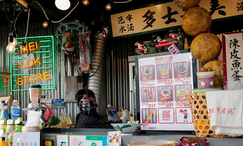 A storekeeper wears gas mask as she sells drink for protesters while the riot police fire tear gas at Tsim Sha Tsui in Hong Kong, China on October 27. — Reuters