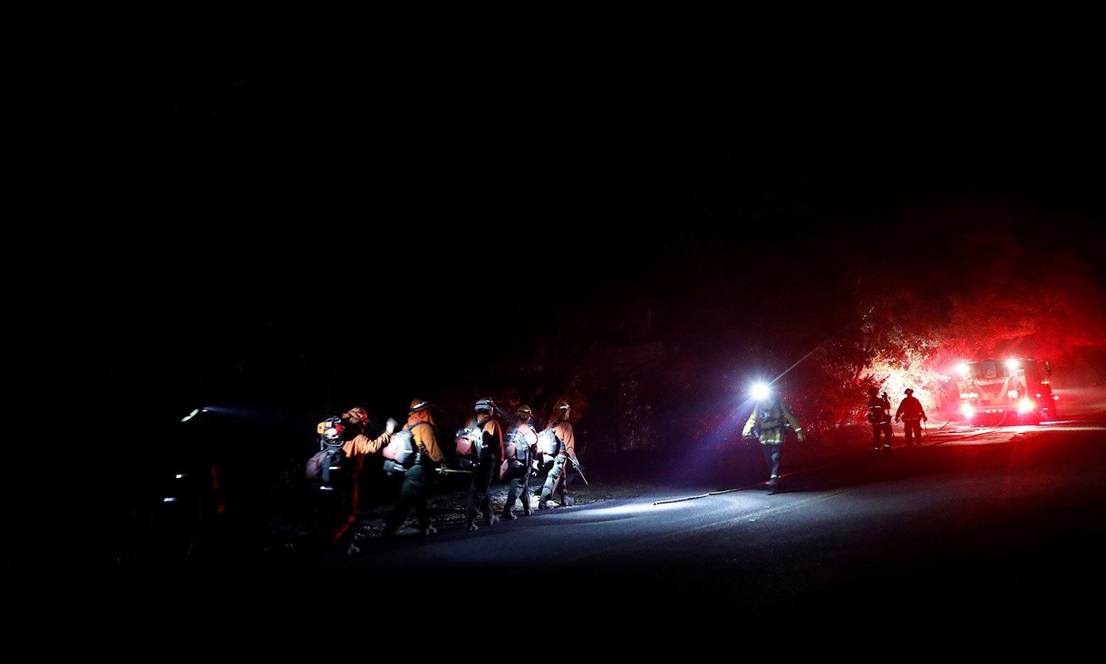عملہ آگ بجھانے کے لیے پہاڑی علاقے کی جانب رواں دواں ہے—فوٹو:رائٹرز