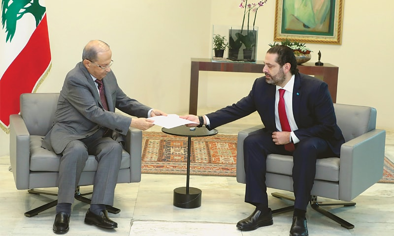 Lebanon's Prime Minister Saad al-Hariri hands over his resignation letter to President Michel Aoun at the Baabda Palace on Tuesday.—Reuters