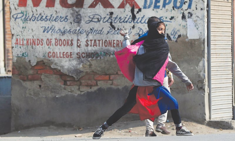 SRINAGAR: A girl throws a stone towards Indian soldiers during a protest on Tuesday.—AP