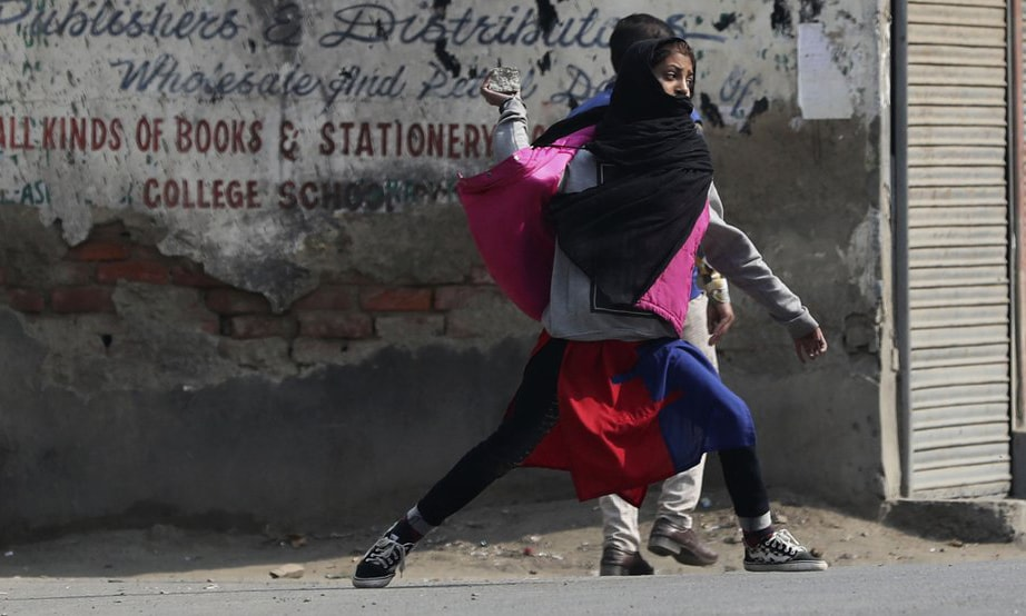 A protesting Kashmiri girl throws stones on Indian policemen in Srinagar on Tuesday, Oct 29. — AP