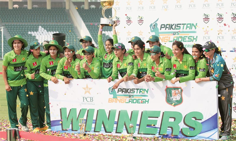 PAKISTAN'S women cricketers celebrate with the trophy after completing the T20 International series whitewash of Bangladesh at the Gaddafi Stadium on Wednesday.—M. Arif/White Star