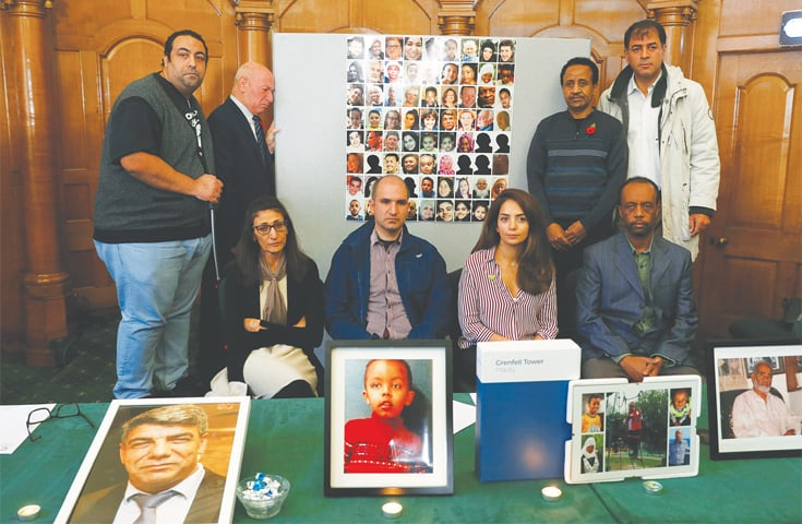LONDON: Relatives of victims of the Grenfell Tower fire pose with pictures during a news conference on Wednesday.—Reuters