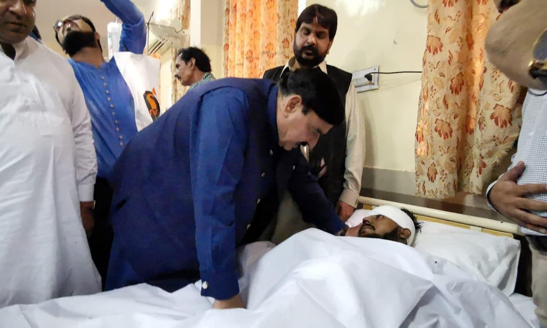 Railways Minister Sheikh Rashid Ahmed asking after a patient at the Sheikh Zayed Hospital in Rahim Yar Khan on Thursday. — Photo provided by Adnan Sheikh