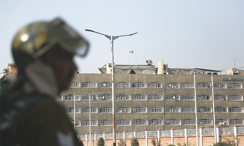 An Indian soldier stands guard as the Indian flag flies atop the government secretariat in Srinagar on Thursday.—AP