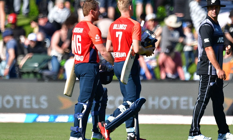England's captain Eoin Morgan (L) and teammate Sam Billings walk from the field after their win in the first Twenty20 cricket match between New Zealand and England at Hagley Oval in Christchurch on November 1. — AFP