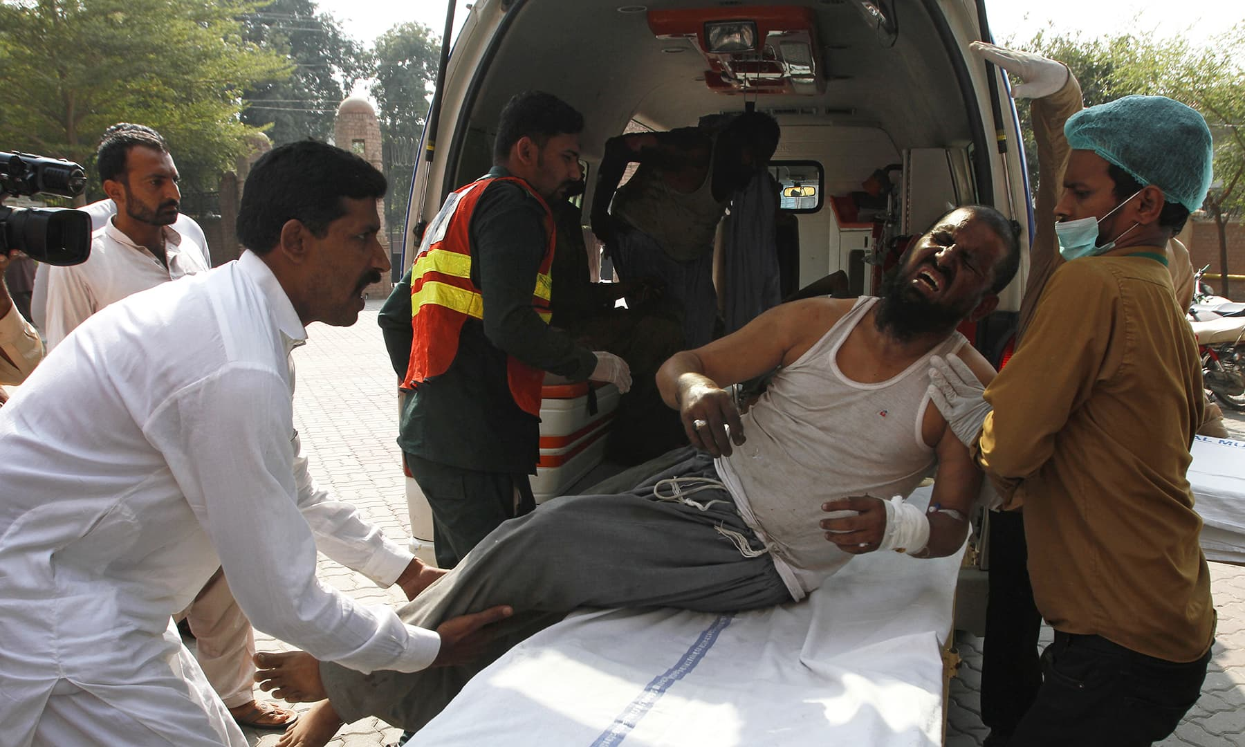 Hospital staff shift a man who was injured in a train fire, to a hospital in Multan on October 31. — AP