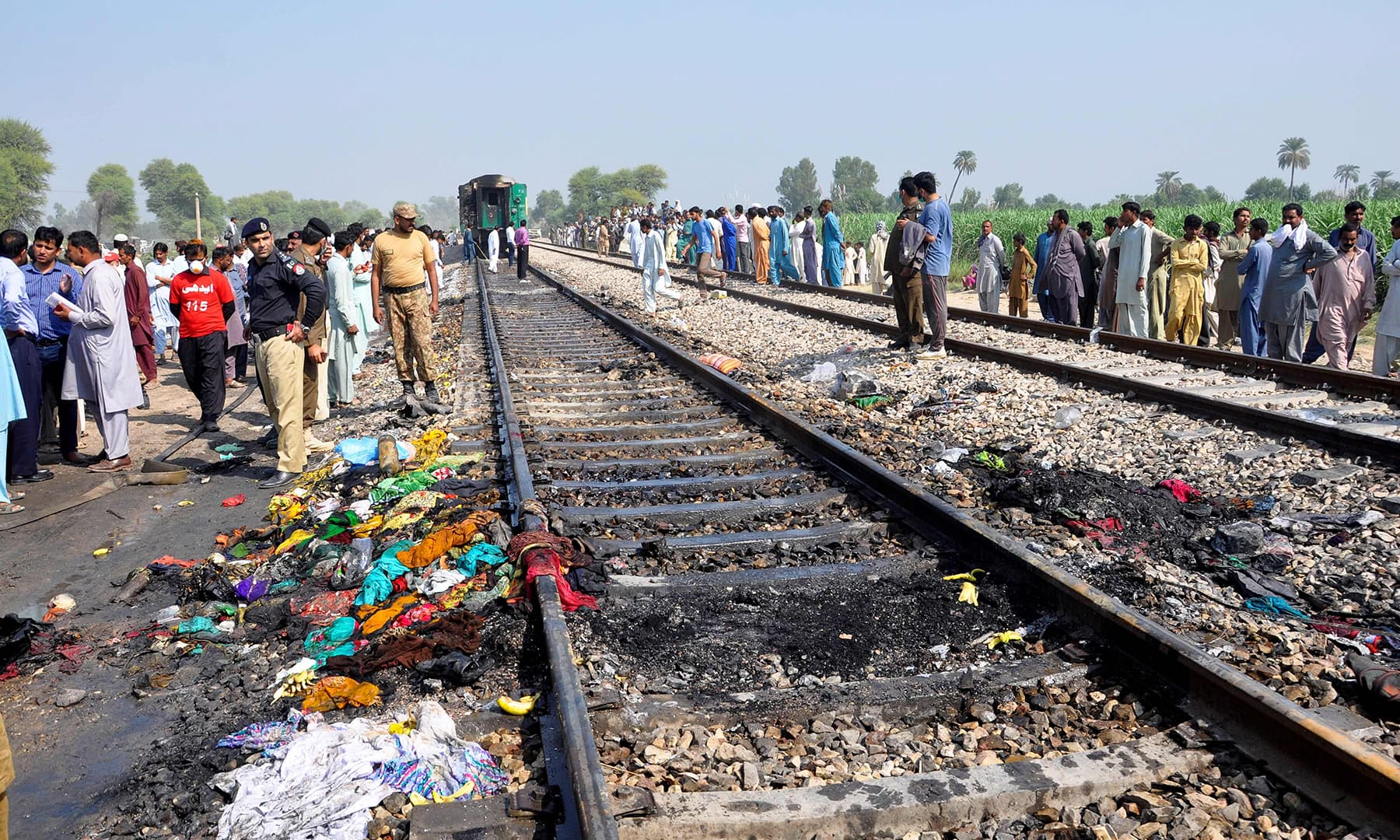 Security personnel and residents gather on a rail track after a passenger train caught on fire near Rahim Yar Khan on October 31. — AFP