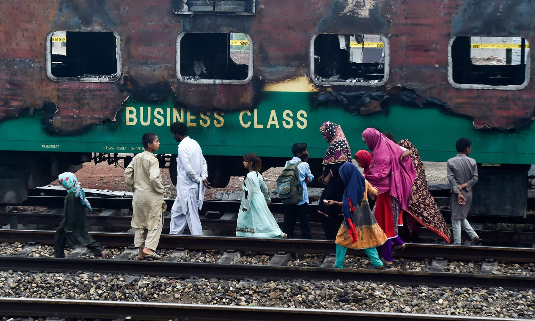 People walk past the burnt-out train carriages a day after a passenger train caught on fire in Rahim Yar Khan on November 1, 2019. — AFP