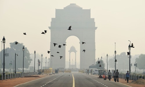 This file photo shows pedestrians walking near the India Gate monument amid heavy smog in New Delhi. — AFP