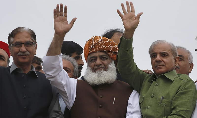 Jamiat Ulema-i-Islam (Fazl) chief Maulana Fazlur Rehman, centre, waves to his supporters with PML-N President Shehbaz Sharif, right, and PPP's Nayyar Bukhari. — AP/File