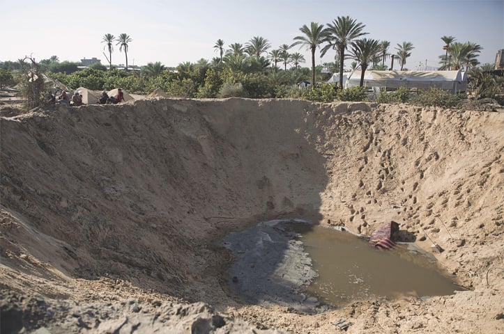 Palestinians sit next to a bomb crater made by an Israeli air strike destroying their farm in the town of Khan Younis, southern Gaza Strip, on Saturday.—AP