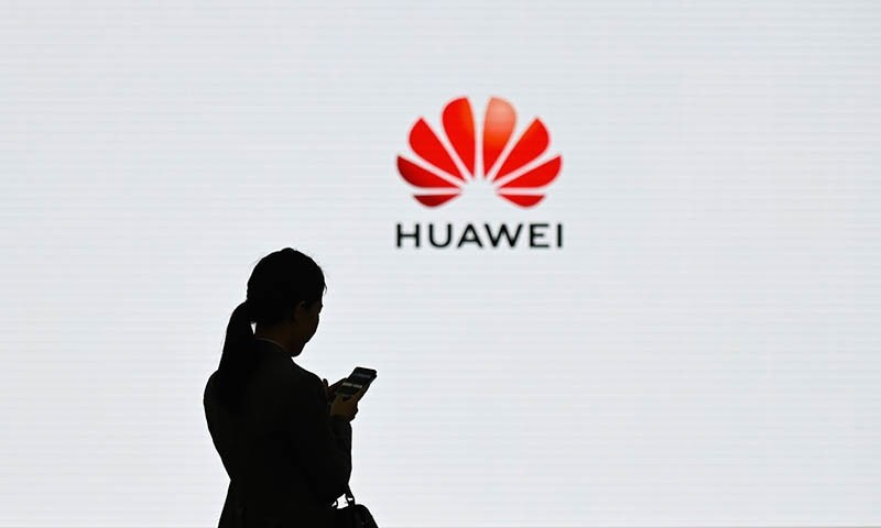In this file photo taken on March 6, 2019 a staff member of Huawei uses her mobile phone. — AFP/File