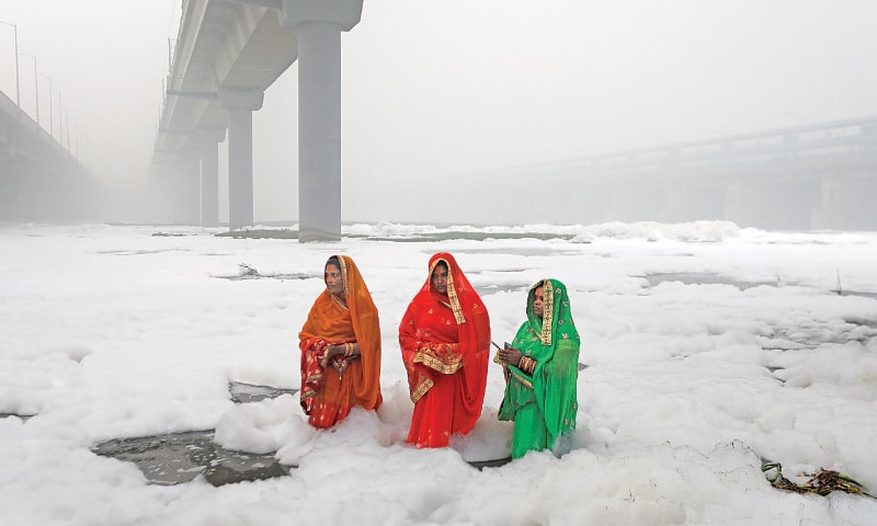 Women worship the Sun deity amid floating foam in the Yamuna River on Sunday.—Reuters