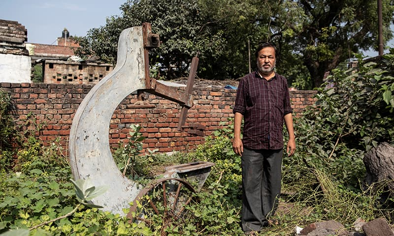 Mohammed Shahid, grandson of Haji Abdul Gaffar, the last imam of Babri mosque, poses in front of a machinery of sawmill which was burnt down by a mob after the demolition of the mosque, in Ayodhya, India. —Reuters