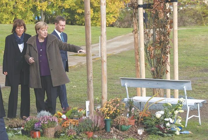 Zwickau: German Chancellor Angela Merkel (second right) pictured after laying flowers at a memorial for victims of a neo-Nazi group, Nationalist Socialist Underground, on Monday.—AP